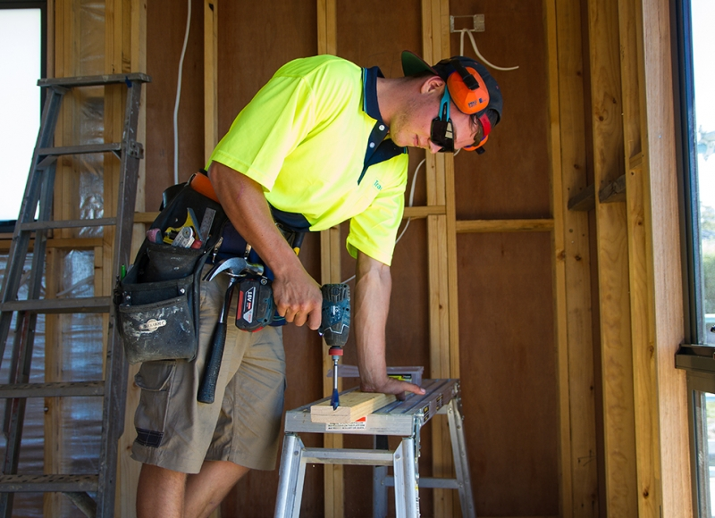 Apprentice using drill at Tasmanian Building Group Apprenticeship scheme